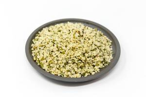 Organic vegan peeled hemp seeds on a black plate