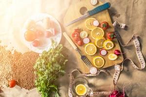 Organisches, vegetarisches Bio-Essen mit Schneidebrett, Maßband, Kräutern und Zitronenscheiben