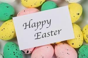 Ostergruß HAPPY EASTER (frohe Ostern) auf weißem Papier liegt auf farbigen Ostereiern