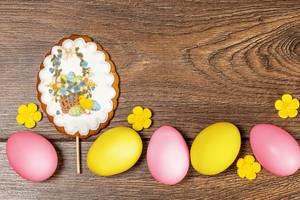Ostern-Lebkuchen und bunte Eier auf hölzernem Hintergrund. Aufnahme von oben