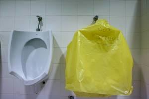 Out of Service - Schriftzug auf gelber Folie zeigt defektes Pissoir neben einem funktionierenden Urinal auf einer Herrentoilette in Barcelona, Spanien