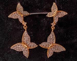 Paar goldene, glitzernde Ohrringe in Schmetterlingsform vor schwarzem Hintergrund