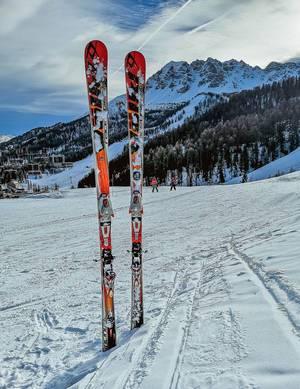 Paar Ski stecken aufrecht in Schnee, dahinter Berge bedeckt mit Schnee zur Wintersaison in Vars, Frankreich