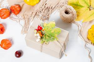 Packaged gift with yellow leaves, berries, scarf and thread on white wooden table. Family holiday concept, Thanksgiving Day (Flip 2019)