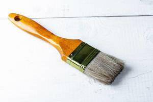 Paint brush on white wooden background