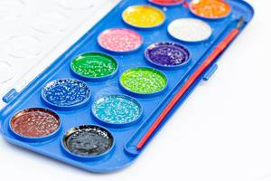 Paint with sequins and brush on white background
