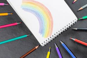 Painted rainbow in a notebook and a variety of colored pencils on a black background (Flip 2019)