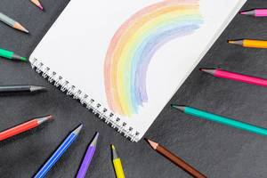 Painted rainbow in a notebook and a variety of colored pencils on a black background