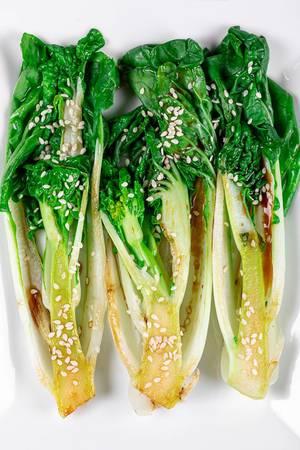 Pak Choi oder Chinesischer Senfkohl mit Sauce und Sesamkörner, Aufnahme von oben vor weißem Hintergrund