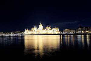 Palace of Parliament in Budapest, reflected in Danube river by night