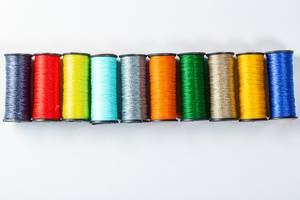 Palette of colored threads on white background
