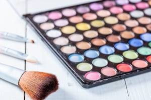 Palette of cosmetic eye shadow with a brushs for application