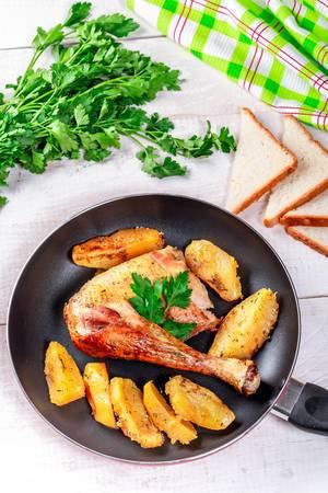 Pan mit gebratenem Hühnerbein und Kartoffeln auf einem weißen Holztisch mit Brot und Kräutern