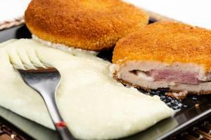 Paniertes Putenfleisch mit Käse-Schinken-Füllung à la Cordon bleu auf einem Teller