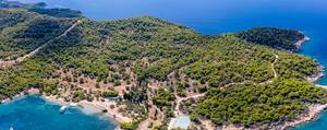 Panoramic picture and aerial view of the Greek island Spetses with its green pine forest and the coast at the blue ocean