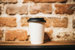 Paper coffee cup on brick wall background