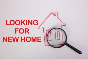 """Papier-Haus mit roter Umrandung auf weißem Hintergrund & Text """"looking for new home"""" - Suche nach einem neuen Zuhause"""