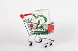 Papierbeutel mit Mehl in Einkaufswagen vor weißem Hintergrund