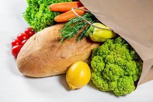 Papiertragetasche-Konzeptbild, mit einem veganen Einkauf mit frischem Brot und Gemüse, auf einem weißem Holzhintergrund