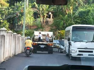 Pärchen fährt auf der Ladefläche eines Transporter mit, durch den Straßenverkehr in Baie Ste Anne auf Praslin, Seychellen