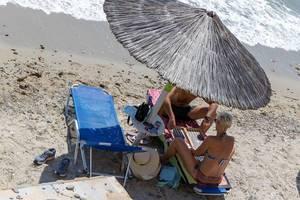 Pärchen unter einem Strohschirm am Strand