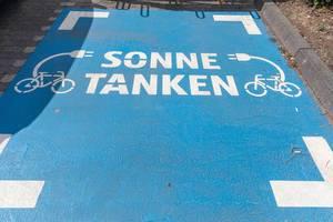 """Parkplatz """"Sonne tanken"""" für Elektrofahrräder auf einem Aldi-Süd Parkplatz"""