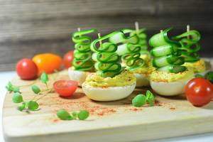 Party food: boiled eggs stuffed and topped by cucumber slices, served on a wooden board with cherry tomatoes and basil leaves