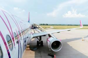 Passagiere steigen in ein WizzAir Flugzeug