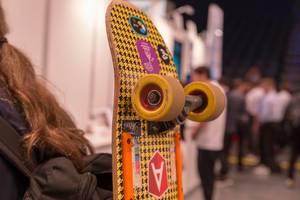 Passant mit einem bunten Skateboard am Rücksack