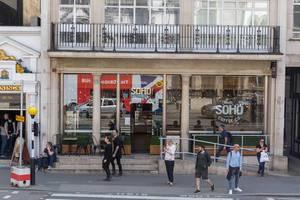 Passanten laufen an einem SOHO Coffee Lokal vorbei