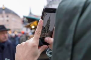 Passantin macht mit Mobiltelefon Foto von Weihnachtsmarkt auf Domplatte mit Kölner Dom