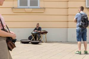 Passersby listening to a young man playing a hang