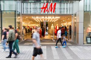 Passersby walking by an H&M outlet
