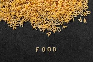 Pasta bildet das Wort Food aus zu Buchstaben geformten Nudeln vor schwarzem Hintergrund