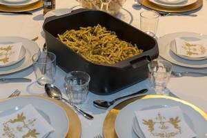 Pasta mit grüner Pestosoße und Kräutern in schwarzem Topf auf festlich gedecktem Tisch