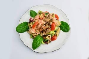Pasta mit Lachs, Tomaten, Sonnenblumenkernen und garniert mit Spinatblättern
