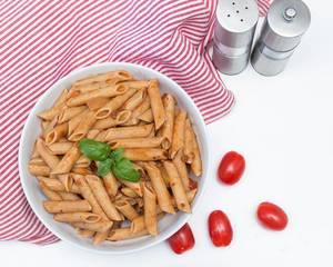 Pasta mit Tomatensoße und Basilikum neben ganzen Cherrytomaten und Salz- und Pfeffermühle