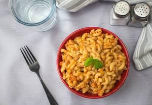 Pasta - Nudeln mit Tomatensoße und Basilikum in einer Roten Schale in der Aufsicht auf einem Tisch mit Gabel, einem Glas Wasser und einem Salzstreuer