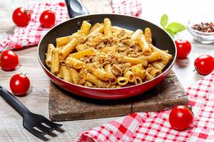 Pasta with minced chicken in a frying pan on a wooden background (Flip 2019)
