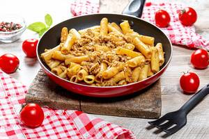 Pasta with minced chicken in a frying pan on a wooden background
