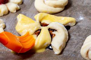 Pastry brush smears beaten egg on raw bun close up (Flip 2019)