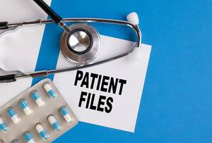 Patient files written on medical blue folder