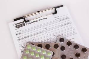 Patient Medical History form with pills on white table