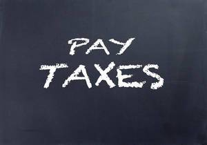 Pay taxes text on blackboard