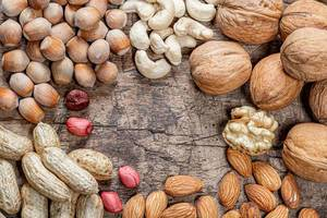 Peanuts, walnuts, almonds, cashews and hazelnuts on old wooden background