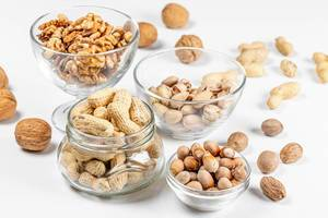 Peanuts, walnuts, pistachios and hazelnuts in glass bowls and in a jar on a white background
