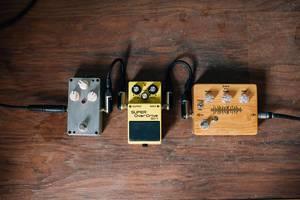 Pedal und weitere Technik zu elektrischer Gitarre auf Holzboden