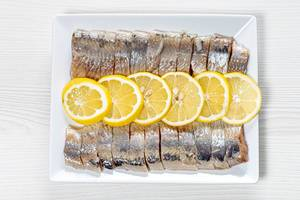 Peeled fillet of pickled herring with lemon slices (Flip 2019)