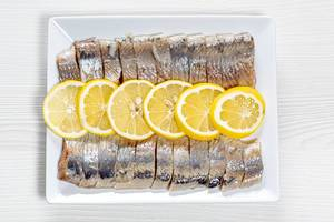 Peeled fillet of pickled herring with lemon slices