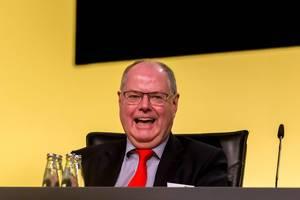 Peer Steinbrück freut sich und lacht auf der Hauptversammlung des BVB